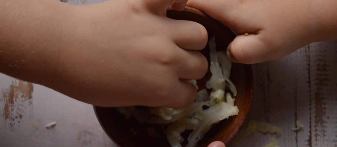 Niños comiendo chucrut, vista de las manos